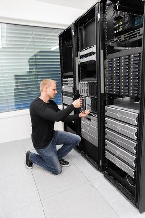Es Ingenieur oder Berater, der mit der Installation von einem Blade-Server in Datenträger. Geschossen im Rechenzentrum.