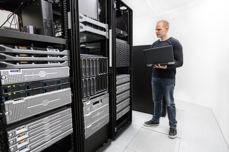 data center: It engineer or consultant standing with a laptop and monitor blade servers in data rack. Shot in datacenter. Stock Photo