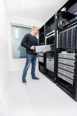 IT support: It engineer or consultant working with installation of a blade server in data rack. Shot in datacenter.