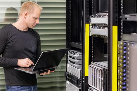 ingeniero: Es ingeniero o consultor de pie con un ordenador portátil y el monitor servidores blade en bastidor de datos. Filmada en centro de datos.