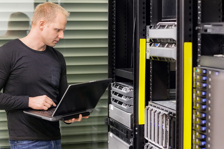 it tech: It engineer or consultant standing with a laptop and monitor blade servers in data rack. Shot in datacenter. Stock Photo