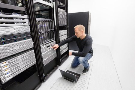 It engineer or consultant working with backup server. Shot in data center. Archivio Fotografico