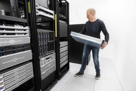 それエンジニアやコンサルタントのインストール ラック マウント型サーバ。データ センターで撮影します。 写真素材