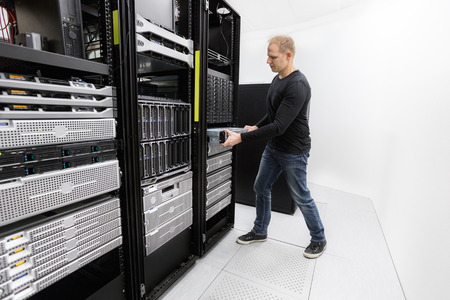 It engineer or consultant installing rack server. Shot in data center.