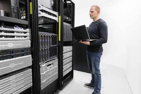 server side: It engineer or consultant standing with a laptop and monitor blade servers in data rack. Shot in datacenter. Stock Photo