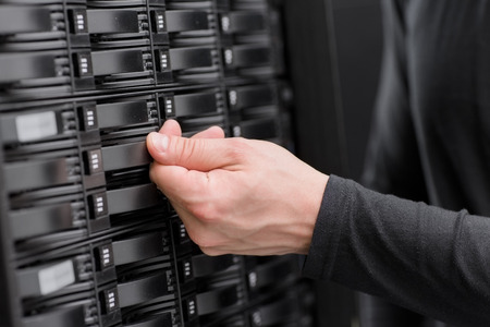 It engineer  technician working in a data center. This enclosures is a SAN (storage area network) and servers bellow. photo