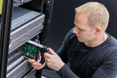 enclosures: E 'ingegnere  tecnico mantenere stoccaggio in data center. Questo recinzioni � una SAN (Storage Area Network) e server. Archivio Fotografico