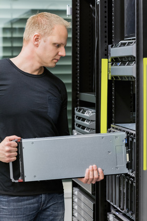 server side: It engineer or consultant working with installation of a blade server in data rack. Shot in datacenter.