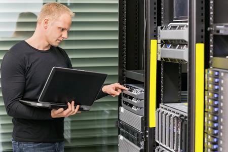 それデータ ラックのノート パソコンとモニターのブレード サーバーとエンジニアやコンサルタントの立っています。データ センターで撮影します