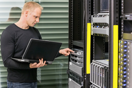 information technology: It engineer or consultant standing with a laptop and monitor blade servers in data rack. Shot in datacenter. Stock Photo