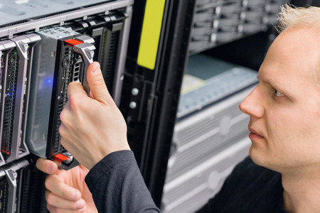 Close up of a it engineer or consultant working with installation of blade server in data rack. Shot in datacenter. photo