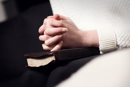 manos orando: Ora mujer cristiana y las manos plegables sobre la Santa Biblia.