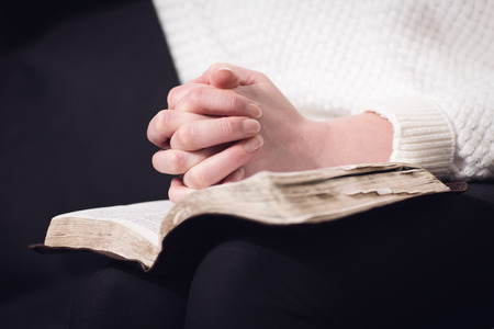 Christian woman pray and folding hands over the holy bible. photo