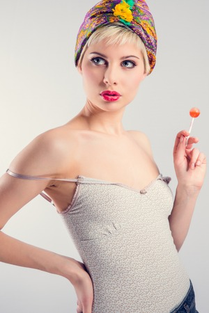 Beautiful young vintage retro looking woman with a lollipop in the hand. photo