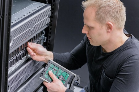 It engineer  technician maintain storage in data center. This enclosures is a SAN (storage area network) and servers. photo