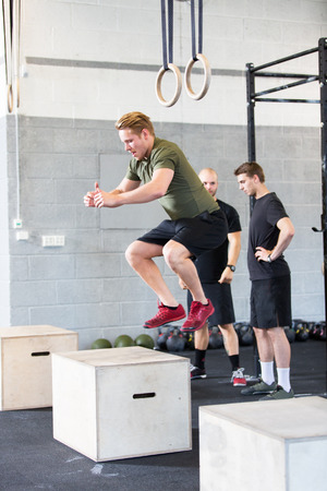 A group trains at a cross fit center. One man do box jumps  photo