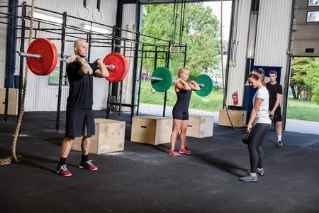 fit on: Un grupo entrena en un centro de forma transversal Peso sesi�n de ejercicios en el gimnasio