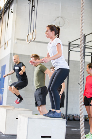A group trains at a cross fit center  Women do box jumps  photo