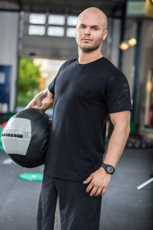 Young trained man with med ball at cross fit center.