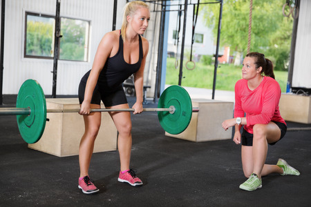 Young woman lift weights with help of a instructor at cross fit center.