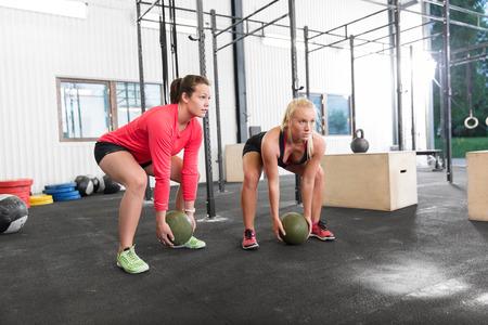Young women lift slam balls at cross fit gym center.