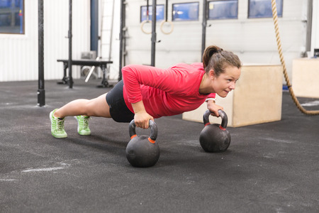 Young hard working women trains push ups at crossfit gym center.