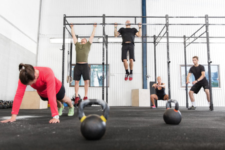 A group training push ups, hang ups and squat at a crossfit center.