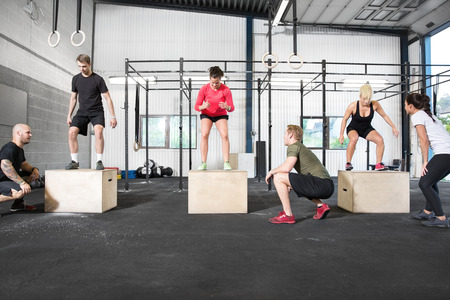 A group trains box jump with personal trainers at a cross fit center.
