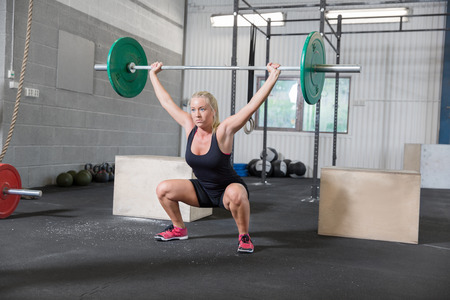 One woman trains at a crossfit center. Squat workout at the gym.