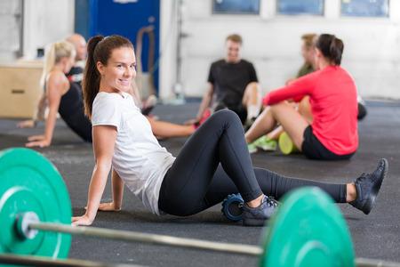 Lachende Frau tut Quer fit Übung für Flexibilität und Mobilität mit einem Yoga-Fitness-Schaumstoffrolle.