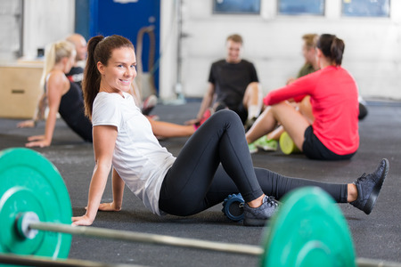 fit on: Mujer sonriente que hace ejercicio en forma cruzada para la flexibilidad y la movilidad mediante un rodillo de espuma de fitness yoga.