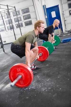 Crossfit センターでスクワットを取って二人の男。体重はジムでトレーニング。
