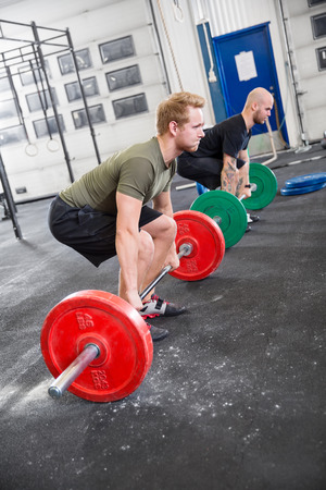Two men taking deadlifts at crossfit center. Weight workout at the gym. Stock Photo