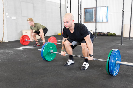 jerk: Two men taking dead lifts or clean and jerk at cross fit center  Weight workout at the gym