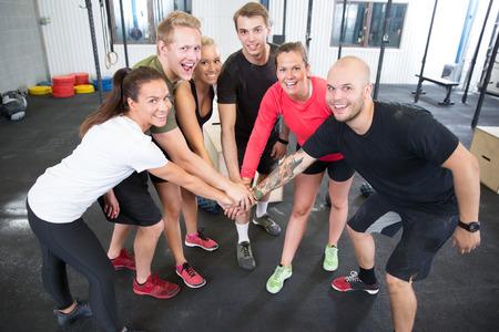 幸せと笑顔の crossfit トレーニング グループ ジム センターで手を繋いでいます。 写真素材