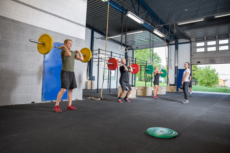 A group trains at a cross fit center. Weight workout at the gym. photo
