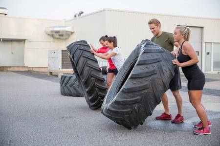 Eine Gruppe oder ein Team Spiegeln schweren Reifen im Freien.