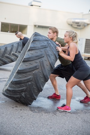 A group or team flipping heavy tires outdoor. Stock Photo
