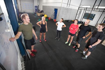 Ein Lehrer geht durch die heutige Trainingsplan in Fitness-Studio.