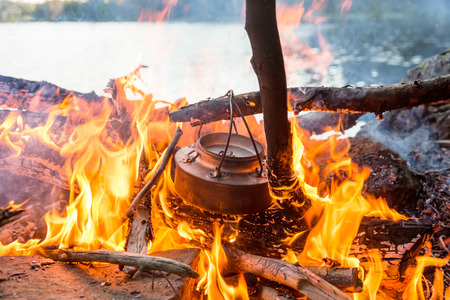 Coffee pot in bonfire close to the seaside. Making coffee outdoor. photo