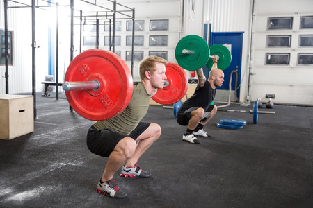 jerk: Two men taking squats at the gym. Weight workout at the gym.