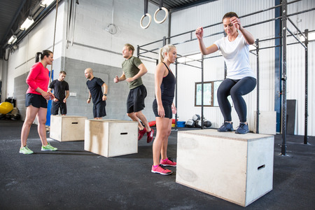 Crossfit group trains box jumps photo