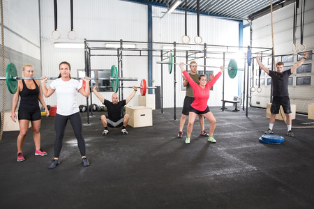 jerk: Team workout with weights at fitness gym center