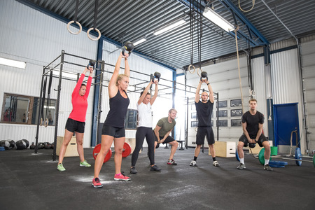 personal trainer: Team workout with kettlebells at fitness gym