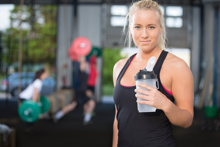 Woman rest and drinking water at fitness gym photo