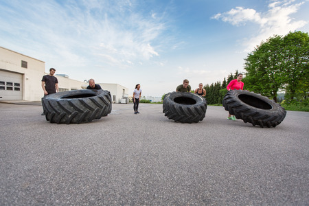 Fitness team flipping heavy tires outdoor Stock Photo