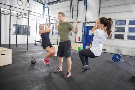 Men exercise: Man trains squats with girls as weights Kho ảnh