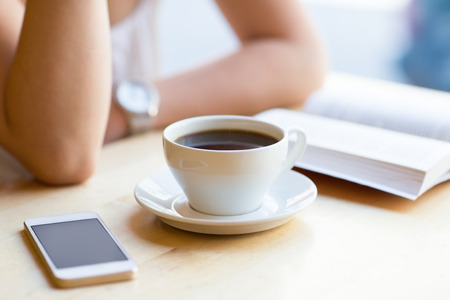 Girl reading book and drinking coffee at cafe