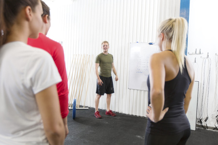 instructs: Personal trainer instructs fitness workout team