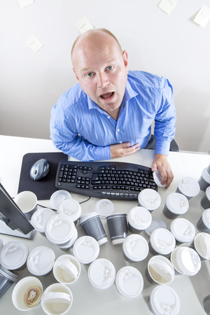 Tired businessman drinks too much coffee at office photo
